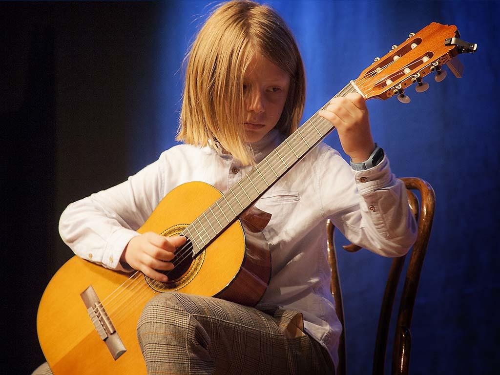 Uczeń grający na gitarze klasycznej